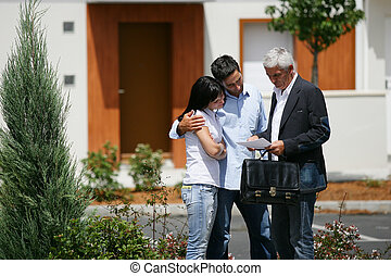 Real estate agent and young couple reading a paper
