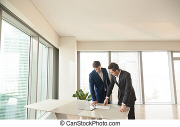 Real estate agent explaining room plan to client