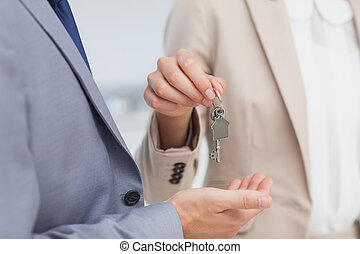 Real estate agent giving house key to a client