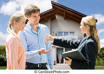 Real Estate Agent Giving House Key To Young Couple