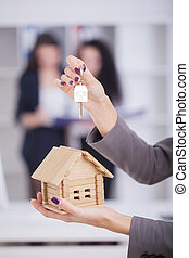 Real estate agent giving house keys to a customer