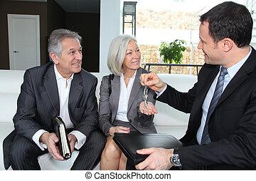 Real-estate agent giving house keys to senior couple