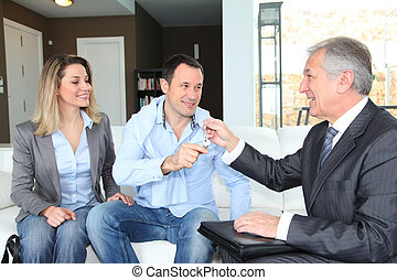 Real-estate agent giving house keys to young owners