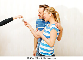 Real estate agent giving keys to the couple