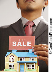 real estate agent holding a sign of for sale and a model house