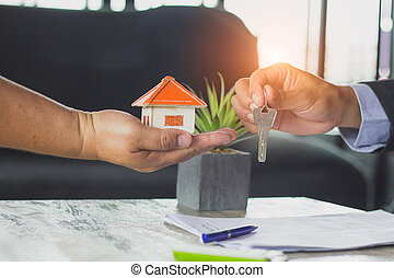 real estate agent holding house key to his client after signing contract agreement in office, concept for real estate, renting property