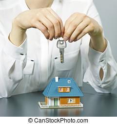 real estate agent holding key above small house model on the table