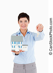 Real estate agent holding keys and a miniature house
