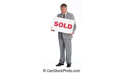 Real estate agent holding sold sign isolated on white...