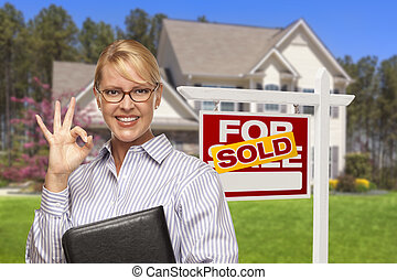 Real Estate Agent in Front of Sold Sign and House - Female...