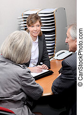 Real estate agent in office with new property owners