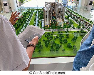 Real estate agent introducing model of residential complex building