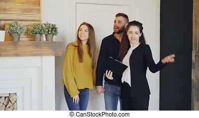 Real estate agent is meeting happy married couple, showing papers and telling them about apartment. Young people are excited, they are looking around and hugging.