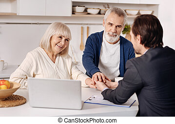 Real estate agent meeting with elderly couple of customers -...