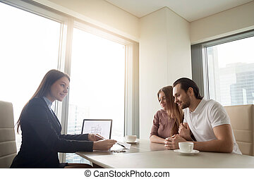 Real estate agent meeting with young couple, applying for mortga