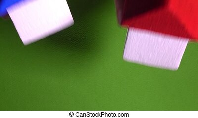 Real estate agent placing toy houses with red and blur roofs against green background. Development concept. 4K video