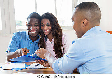Real estate agent presenting contract to african american couple