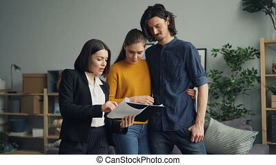 Real estate agent showing documents to man and woman, people...