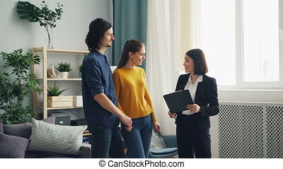 Real estate agent showing new house to buyers talking discussing contract