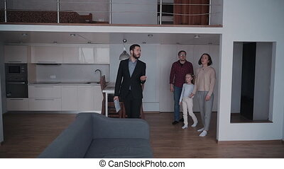 Real estate agent showing new house to happy family of three...
