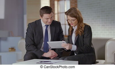 Real estate agent showing photos on tablet to businessman...