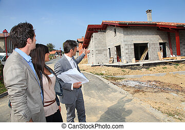 Real-estate agent showing plan to young home investors