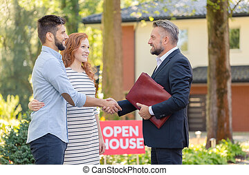 Real estate agent welcoming couple