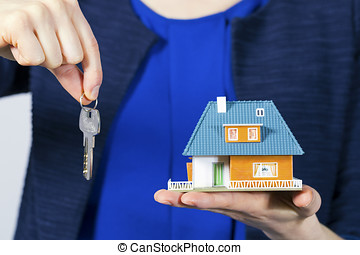 real estate agent with key and house model on hand