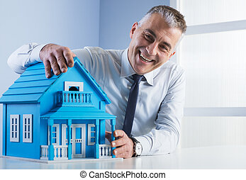 Real estate agent with model house