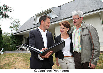 Real-estate agent with senior couple buying new house