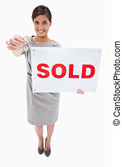 Real estate agent with sold sign handing over key