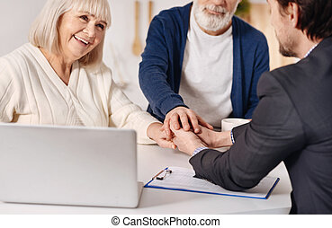 Real estate agent working with elderly couple of customers -...
