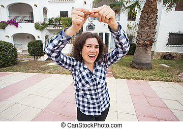 Real estate and property concept - Happy young woman in front of new home with new house keys