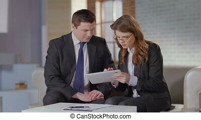 Real estate broker showing photos to client, business meeting