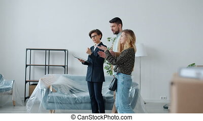 Real estate broker is using tablet and showing new house to buyers man and woman talking gesturing touching device screen. People and sales business concept.
