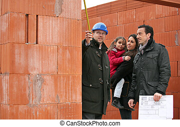 real estate businessman and a family on a construction site