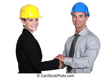 real estate businesswoman and businessman shaking hands
