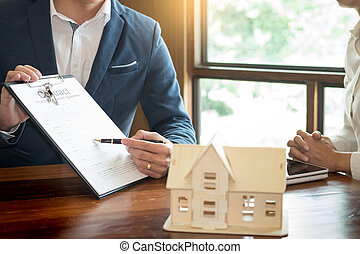 Real Estate concept, Agent to present the property? price for loan investment chart graph documents and calculating table payment to customer.