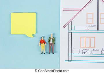 Real Estate concept. Construction building. Blank speech bubbles, people toy figures, paper model house, blueprints with key on blue architect desk table background. Top view. Copy space for ad text.