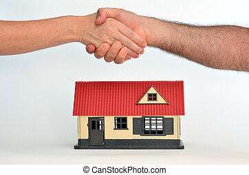 Real Estate Concept - Man and a woman shaking hands over a...