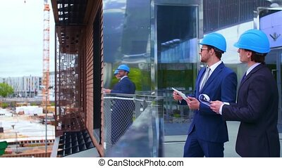 Real estate developers in helmets. New office construction....