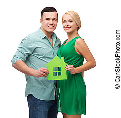 smiling couple holding green paper house