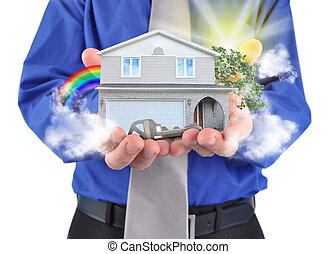 Real Estate House in Hands - A man is holding a house in his...