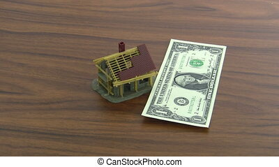 Real estate - One Dollar notes falling on a model house