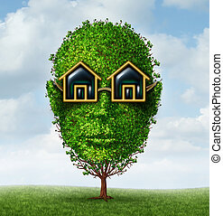 Real estate planning concept as a green tree shaped as a human head with eye glasses in the shape of a home or house as a symbol of visionary investment strayegy for a growing new residential construction project.