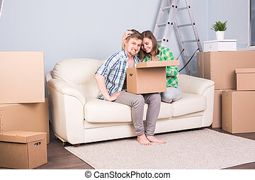 Real estate, relocation and moving concept - young couple holding a cardboard sitting on sofa