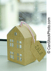 Real estate sale concept, paper model of residential building.