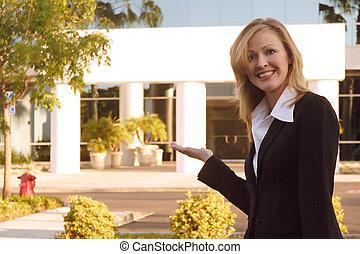 Real Estate sales broker presenting building