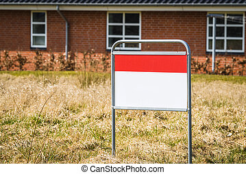 Real estate sign on a lawn in front of a house
