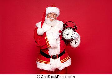 Real jolly Santa Claus holding alarm clock.